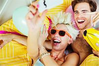 Couple taking self-portraits in bed at party Stock Photo - Premium Royalty-Freenull, Code: 6113-07542992
