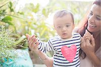 Mother helping baby boy walk outdoors Stock Photo - Premium Royalty-Freenull, Code: 6113-07543271