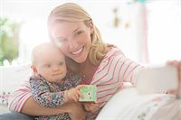 Mother taking self-portrait with baby girl Stock Photo - Premium Royalty-Freenull, Code: 6113-07543283