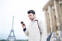 Businessman using cell phone by Eiffel Tower, Paris, France Stock Photo - Premium Royalty-Freenull, Code: 6113-07543404