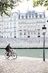 Man riding bicycle along Seine River, Paris, France