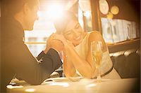 Couple holding hands in restaurant Stock Photo - Premium Royalty-Freenull, Code: 6113-07543540