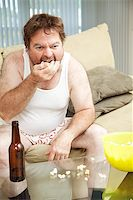 Middle aged man at home on the couch watching tv, drinking beer, and eating popcorn, in his underwear. Stock Photo - Royalty-Freenull, Code: 400-07554264