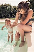 Mother and baby daughter paddling in swimming pool Stock Photo - Premium Royalty-Freenull, Code: 649-07559772