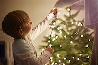 Young boy putting up christmas tree lights Stock Photo - Premium Royalty-Freenull, Code: 649-07559802