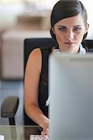 Young office worker using computer Stock Photo - Premium Royalty-Freenull, Code: 649-07560063