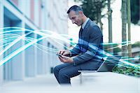 streaming - Waves of blue light and businessman texting on smartphone Stock Photo - Premium Royalty-Freenull, Code: 649-07560155