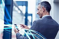 streaming - Waves of blue light and businessman using touchscreen on smartphone Stock Photo - Premium Royalty-Freenull, Code: 649-07560158
