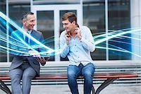streaming - Businessman and young man watching digital tablet and waves of blue light Stock Photo - Premium Royalty-Freenull, Code: 649-07560161