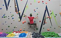 Route setter trying bouldering problem at indoor climbing wall Stock Photo - Premium Royalty-Freenull, Code: 649-07560193