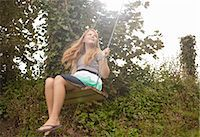 Girl daydreaming on garden swing Stock Photo - Premium Royalty-Freenull, Code: 649-07560219