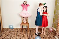 Three girls playing hide and seek at birthday party Stock Photo - Premium Royalty-Freenull, Code: 649-07560312