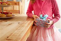 Girl holding birthday present, mid section Stock Photo - Premium Royalty-Freenull, Code: 649-07560317