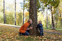 Father and son playing at bottom of tree Stock Photo - Premium Royalty-Free, Artist: Blend Images, Code: 649-07560335