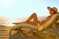 Woman Sunbathing on Recliner Chair at Sunset Stock Photo - Premium Rights-Managed, Artist: ableimages, Code: 822-07562574