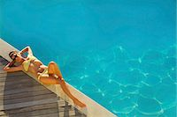 Woman Sunbathing by Swimming Pool, High Angle View Stock Photo - Premium Rights-Managednull, Code: 822-07562583