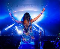 Cheering woman with glow sticks on man's shoulders at music festival Stock Photo - Premium Royalty-Freenull, Code: 6113-07564765