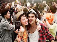 Couple taking self-portrait at music festival Stock Photo - Premium Royalty-Freenull, Code: 6113-07564926
