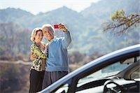 Senior couple taking self-portrait with cell phone outside car Stock Photo - Premium Royalty-Freenull, Code: 6113-07565001