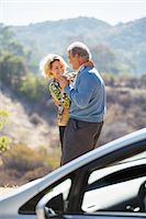 Happy senior couple dancing at roadside outside car Stock Photo - Premium Royalty-Freenull, Code: 6113-07565011