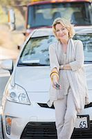 Portrait of smiling woman waiting for roadside assistance Stock Photo - Premium Royalty-Freenull, Code: 6113-07565020