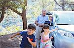 Grandparents watching grandchildren running outside car