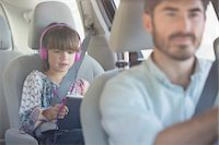 Girl with headphones using digital tablet inside car Stock Photo - Premium Royalty-Freenull, Code: 6113-07565059