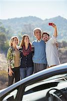 road trip - Family taking self-portrait with cell phone outside car Stock Photo - Premium Royalty-Freenull, Code: 6113-07565090