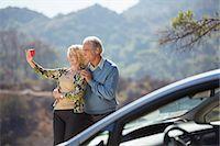 Senior couple taking self-portrait at roadside outside car Stock Photo - Premium Royalty-Freenull, Code: 6113-07565113
