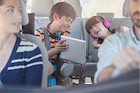 Happy brother and sister using digital tablet in back seat of car Stock Photo - Premium Royalty-Freenull, Code: 6113-07565122