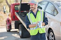 Roadside mechanic wiping hands with cloth next to tow truck Stock Photo - Premium Royalty-Freenull, Code: 6113-07565134