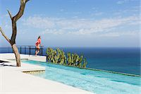 rich lifestyle - Woman standing on poolside balcony overlooking ocean Stock Photo - Premium Royalty-Freenull, Code: 6113-07565217