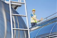 side view tractor trailer truck - Worker using laptop on platform above stainless steel milk tanker Stock Photo - Premium Royalty-Freenull, Code: 6113-07565362