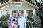 Portrait of smiling multi-generation men outside house