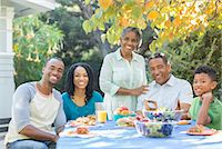Portrait of smiling multi-generation family eating lunch on patio Stock Photo - Premium Royalty-Freenull, Code: 6113-07565506