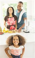 Portrait of enthusiastic girl in kitchen with parents in background Stock Photo - Premium Royalty-Free, Artist: Robert Harding Images, Code: 6113-07565613