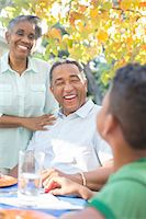 Grandparents and grandson laughing at patio table Stock Photo - Premium Royalty-Freenull, Code: 6113-07565647