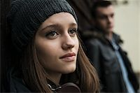 Close-up portrait of teenage girl outdoors, wearing hat and headphones around neck, with young man in background, Germany Stock Photo - Premium Royalty-Freenull, Code: 600-07567384