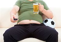 fat man drinking beer  and sitting on sofa to watch TV Stock Photo - Royalty-Freenull, Code: 400-07575401