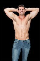 Happy muscular man posing in blue jeans on black background Stock Photo - Royalty-Freenull, Code: 400-07584259
