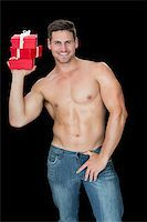 Muscular man holding pile of presents in blue jeans on black background Stock Photo - Royalty-Freenull, Code: 400-07584276