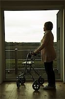 Senior woman using walker, standing and looking out of window, Germany Stock Photo - Premium Rights-Managednull, Code: 700-07584815