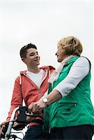 Teenage grandson talking to grandmother using walker in park, Germany Stock Photo - Premium Rights-Managednull, Code: 700-07584820