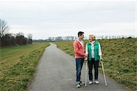Teenage grandson talking to grandmother using crutches on pathway in park, walking in nature, Germany Stock Photo - Premium Rights-Managednull, Code: 700-07584831