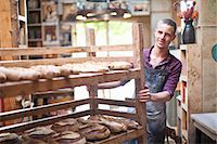 Portrait of young male baker with shelves of fresh bread Stock Photo - Premium Royalty-Freenull, Code: 649-07585068