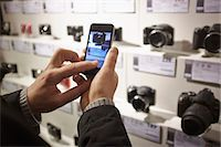 Mid adult man photographing camera's in shop display using smartphone Stock Photo - Premium Royalty-Freenull, Code: 649-07585105