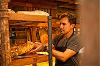 Mature man placing fresh bread on shelf Stock Photo - Premium Royalty-Freenull, Code: 649-07585190
