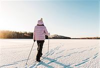 Woman nordic walking through snow covered field Stock Photo - Premium Royalty-Freenull, Code: 649-07585217