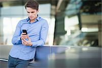 Mid adult man leaning against wall reading texts on smartphone Stock Photo - Premium Royalty-Freenull, Code: 649-07585395