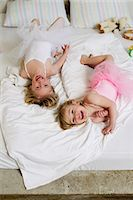 Portrait of two young sisters playing on bed Stock Photo - Premium Royalty-Freenull, Code: 649-07585455